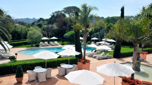 The hotel was once a private villa and still feels like one, surrounded by olive trees and lawns, and reflected in a ...