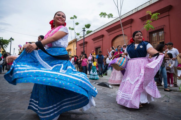 Women in traditional costume dancing for Guelaguetza celebration, Oaxaca, Mexico.