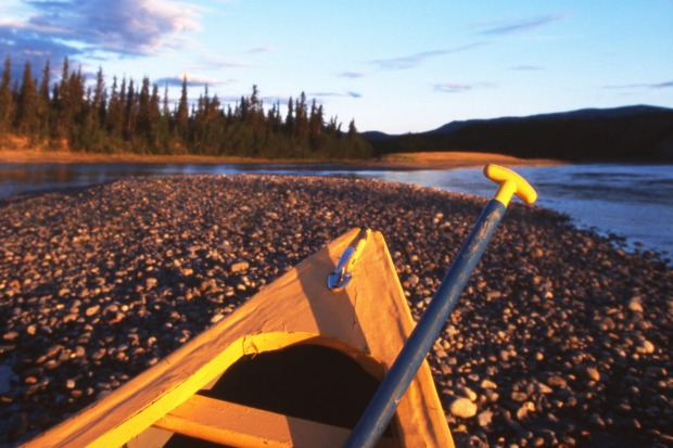 The view of the bow of a canoe during a trip down the Yukon River, Canada.