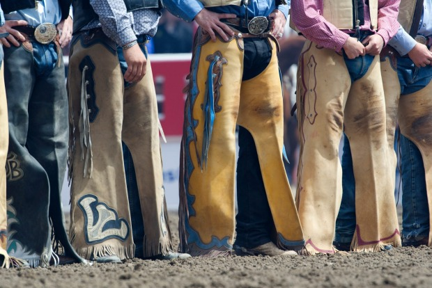 Cowboys wearing chaps at Calgary Stampede rodeo.