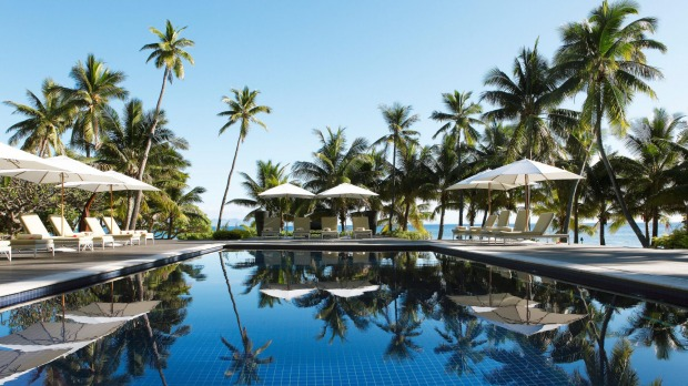 Sun loungers and parasols by the pool at Vomo Island Resort.