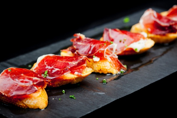 "Typical Spanish snack of cured ham and bread. Tapas are (it's plural, the singular is tapa, which means ""lid"") as much ..."