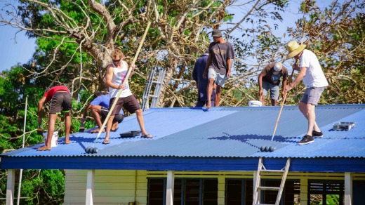 Volunteers repairing and repainting roofs.