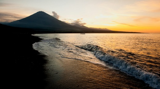 The active volcano, Gunung Agung, looms large in the background of this sunset beach scene taken in Jemeluk, Amed, Bali.