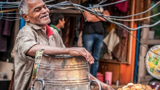 Man is having laugh at his food stall at the Old Delhi spice market.
