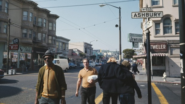 Pedestrians walking along a sidewalk by the intersection of Haight and Ashbury streets in the Haight-Ashbury district of ...