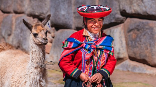 Peruvian girl wearing national clothing walking her llama.