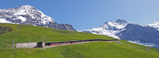 A train passes through a tunnel in Switzerland under Eiger Mountain (the famous North Face) and Jungfrau Peak on its way ...