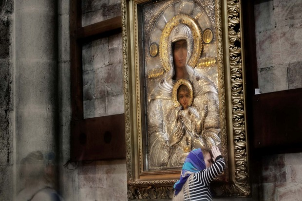 A pilgrim by the Virgin Mary with Child icon in the Catholicon in Holy Sepulchre Church in Jerusalem.