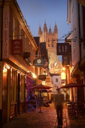 Shopping in Canterbury's cobbled backstreets, with the grand Cathedral tower illuminated at twilight, Canterbury, Kent, ...