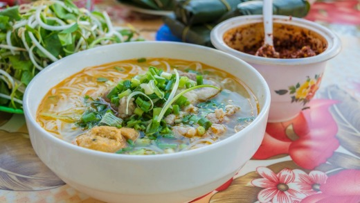 The aroma of the bun bo (beef noodle soup) is tantalisingly strong in our open-air eatery.