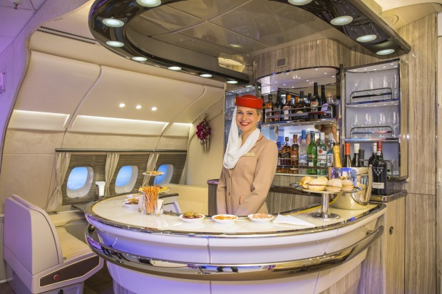 An Emirates Airlines cabin crew attendant stands in the new bar area for the Airbus A380 aircraft during the unveiling ...