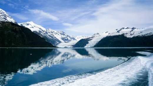 Glaciers flow down from the mountains into the water next to the rocky cliffs of Prince William Sound.