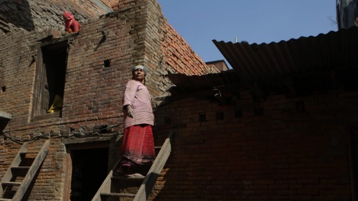 A woman works on reconstructing her house in Bhaktapur, Nepal, after it was damaged by the 2015 earthquake.