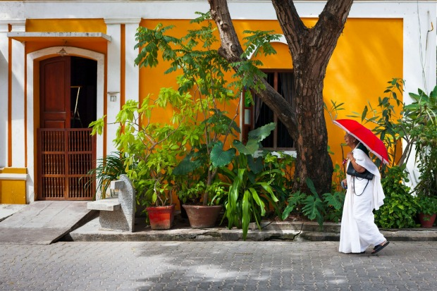 A widow in white sari walks past a colorful house in Pondicherry.