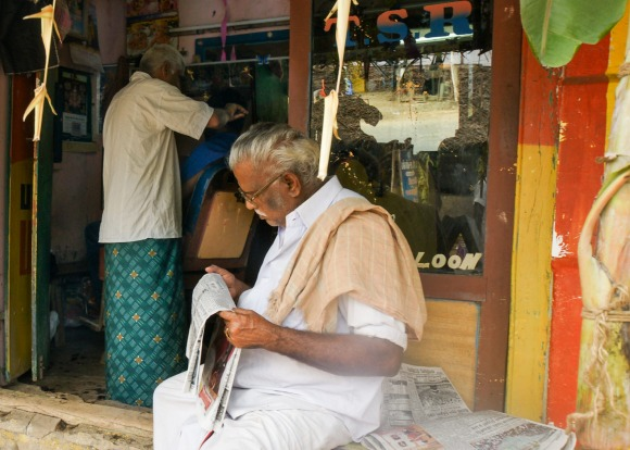 A man reads the newspaper while waiting his turn at the barber shop.