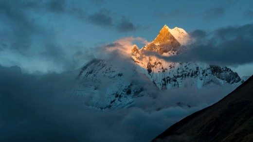 View on the summit of the mountain Machapuchare at sunset, partly covered by monsoon clouds.