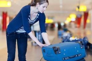 Woman picked up luggage at airport carousel.