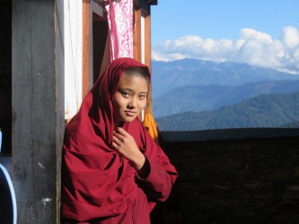 Student nun at the Kila Gompa nunnery in Bhutan.   The Buddhist  nunnery is situated on a cliff side high above the Paro ...