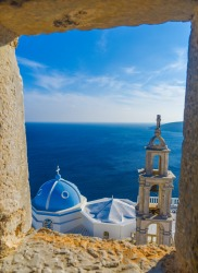 Panagia Portaitissa monastery viewed from a window of Querini's Venetian Castle, Astypalea Island, Greece.After taking ...