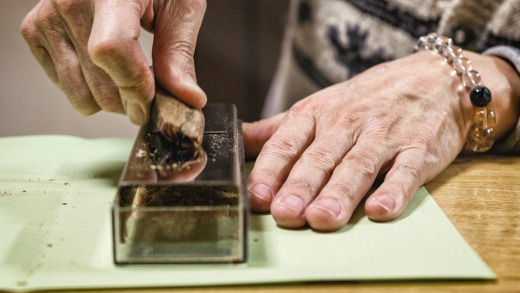 A Japanese man shaves a piece of bonito fish to create flakes used for seasoning in Japan.