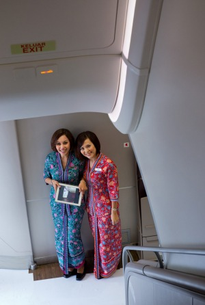 Malaysia Airlines cabin crew at the bottom of the A380 staircase.