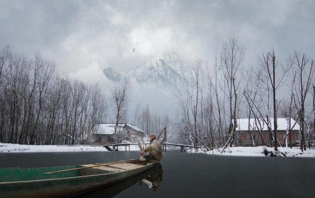 In one of the many beautiful lakes found in Kashmir, a  local fisherman is taking a swiff of his shisha while his boat ...