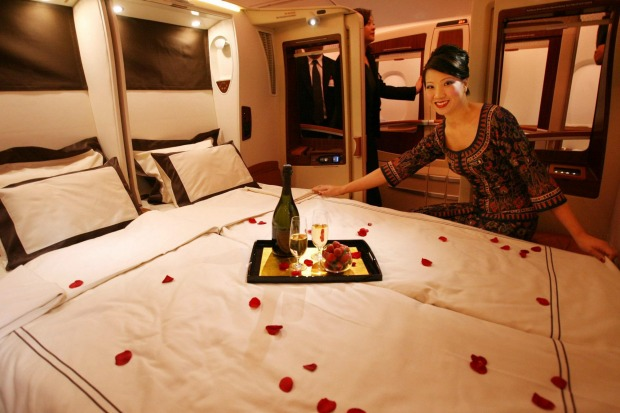 A Singapore Airlines stewardess straightens the duvet cover on one of two double beds aboard the Airbus A380 superjumbo.