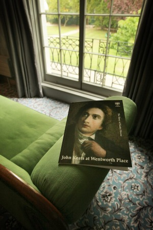 A brochure showing a portrait of John Keats sits on a chaise lounge.