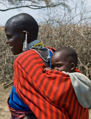 A local woman with a little child carried in traditional way walks through Ngorongoro Park, Tanzania.