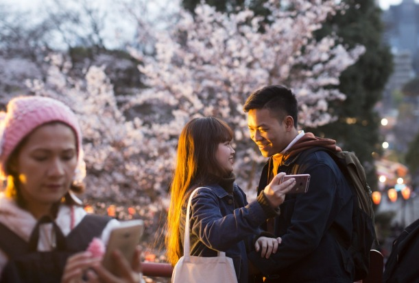 A couple from Vietnam, right, takes a selfie photograph in front of a cherry tree in blossom in Tokyo, Japan. Japan's ...