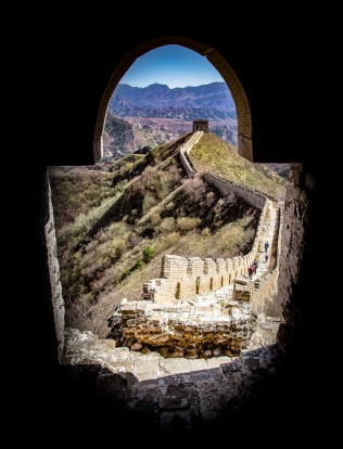 View from a tower on the great wall of China, showing the wall disappearing off into the distance towards the mountain range.