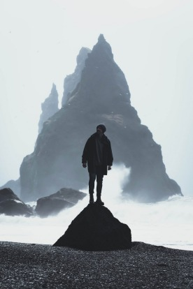 Admiring the towering cliffs and violent surf of Reynisfjara black sand beach in Iceland. The diversity of landscapes ...