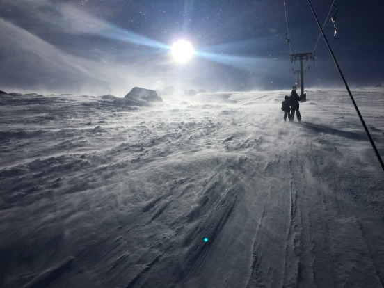 Thredbo ski lift on a windy day looking into the sun.