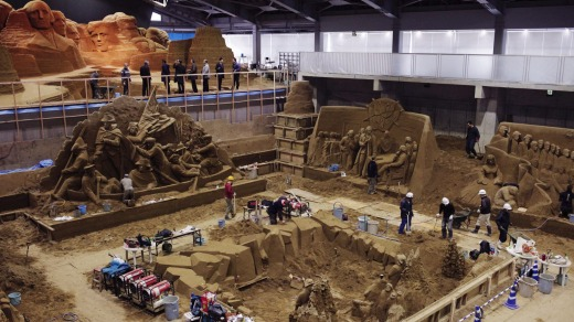 Artists and staff work inside the sand museum.
