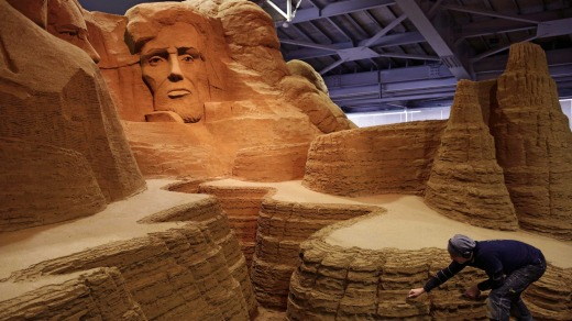 Leonardo Ugolini works on a sculpture inspired by Mount Rushmore's four presidents at the sand museum.