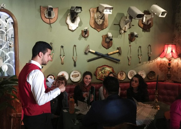 A waiter serves customers seated in front of mounted security cameras and slingshots at The Walled Off Hotel.