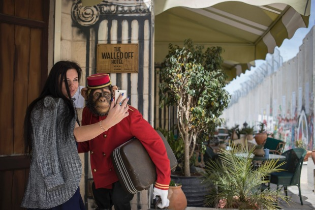 A tourist takes a selfie with the plastic greeter chimp at the entrance of The Walled Off Hotel.