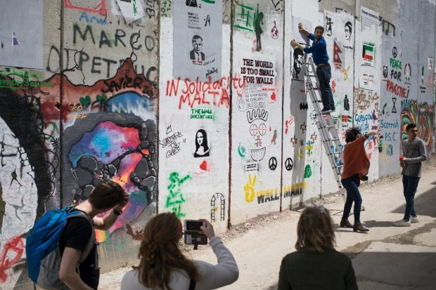 Visitors paint on the Israeli security barrier outside of The Walled Off Hotel.