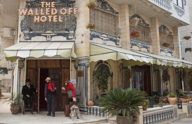 A hotel employee opens the door for a visitor at The Walled Off Hotel, opposite the Israeli security barrier in ...