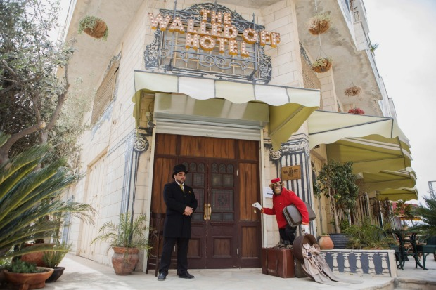 A hotel employee stands next to the plastic greeter chimp at The Walled Off Hotel.