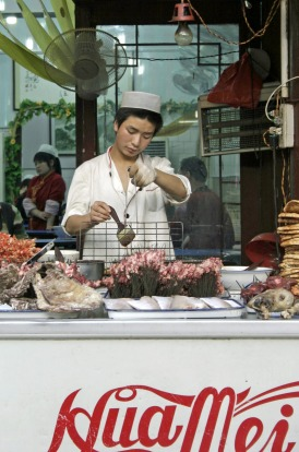 A Muslim street vendor selling snacks on Beiyuanmen street in Xian, China.