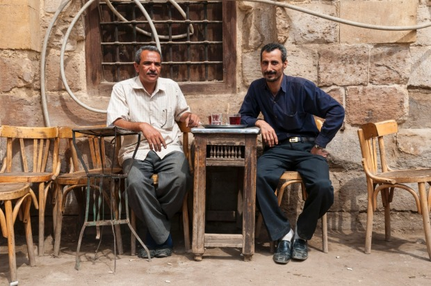 Two locals sit at a rustic neighborhood cafe set up on the street in Cairo, Egypt.