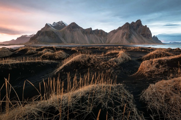 Black sand dunes illuminated by the setting sun beneath the cliffs of Batman Mountain in Iceland.