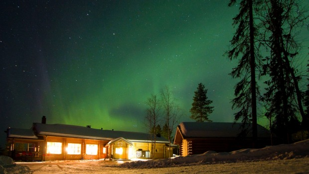 Aurora borealis, or Northern Lights, moving across the night sky at Winter basecamp Oulanka National Park.