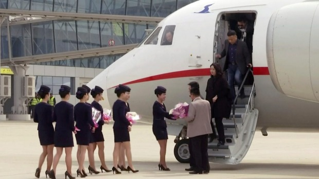 Air Koryo cabin crew greet passengers with flowers at Pyongyang's Sunan airport last month as the first Air Koryo flight ...
