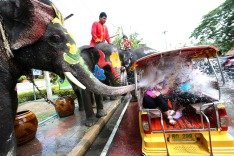 In this Tuesday, April 11, 2017 photo, with assist from its mahouts, elephants blow water from its trunk to tourists on ...