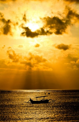 Beautiful orange sky Bali Sunset with traditional fishing boat in the foreground.