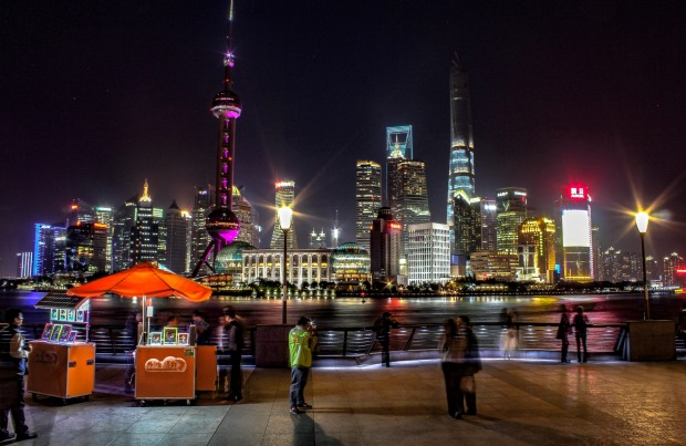 People enjoying the Bund, with the Shanghai city skyline in the background.