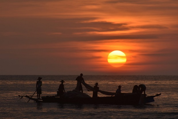 Net-fishing at sunset at Ngswe Saung Beach, west coast of Myanmar.